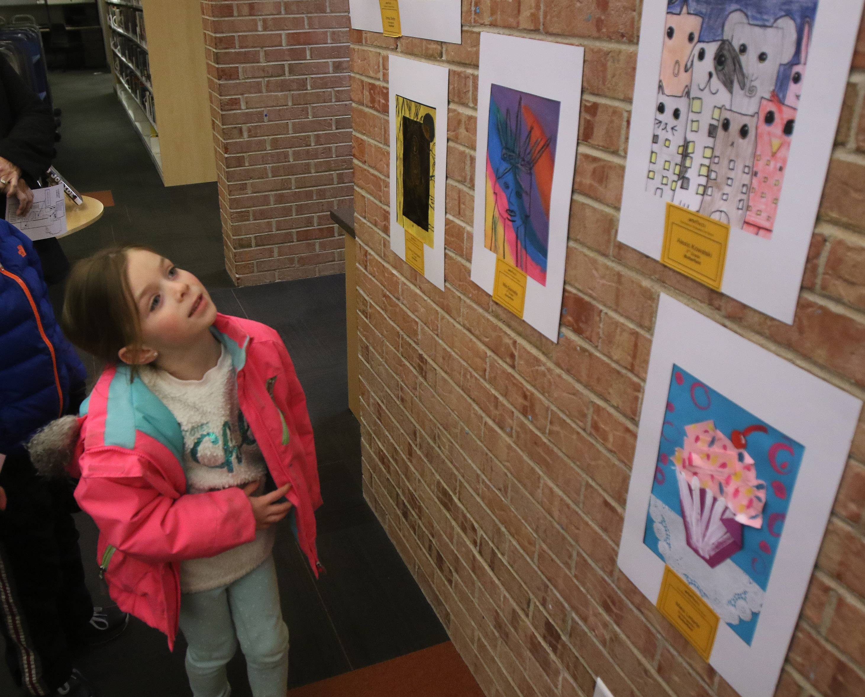 "Butterfield kindergartner Emma Shafer looks at her classmates art pieces during the seventh annual ""art effects"" art show Thursday at Cook Park Public Library in Libertyville. About 150 students from Libertyville School District 70 had their artwork on display."