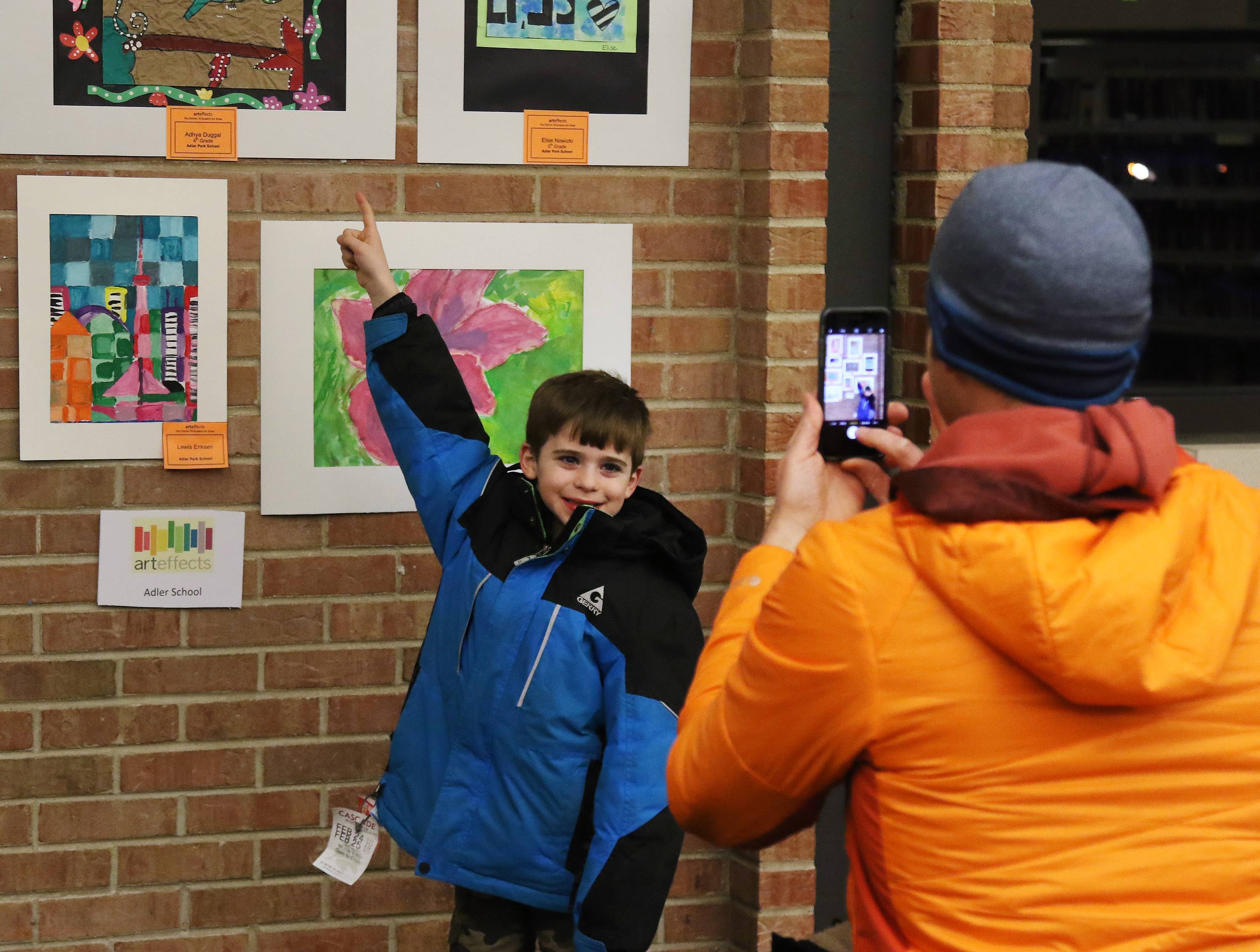 "Adler Park kindergartner Danny Kiefer has his picture taken by his father, Ben, with his art piece during the seventh annual ""art effects"" art show Thursday at Cook Park Public Library in Libertyville. About 150 students from Libertyville School District 70 had their artwork on display."