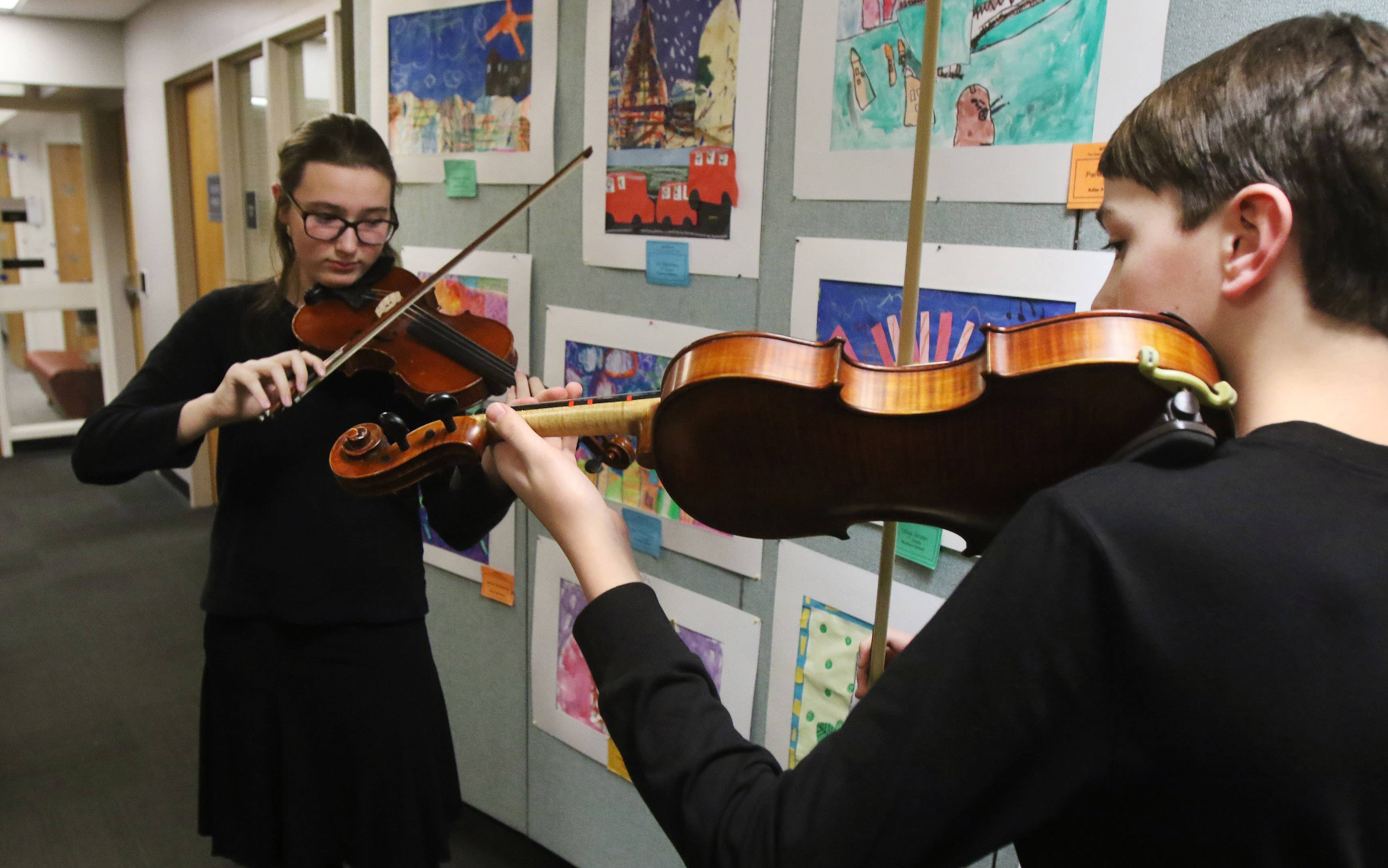"Highland Middle School students Anna Koberstein, left, and Michael Lothspeich play violins as they practice before performing at the seventh annual ""art effects"" art show Thursday at Cook Park Public Library in Libertyville. About 150 students from Libertyville School District 70 had their artwork on display."