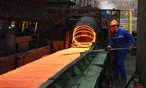 "In this March 5, 2018 photo, a worker manipulates coils of steel at Xiwang Special Steel in Zouping County in eastern China's Shandong province. China says it ""firmly opposes"" U.S. President Donald Trump's tariff increase for imported steel and aluminum but gave no indication whether Beijing might impose its own measures in response. (Chinatopix via AP)"