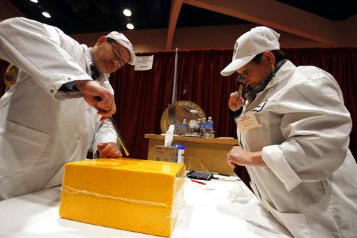 Judges Lars Johannes Nielsen and Kerry Kaylegian inspect a cheddar, aged one to two years, during the World Championship Cheese Contest, Tuesday, March 6, 2018, in Madison, Wis. The biennial event started Tuesday and runs through Thursday night. Organizers say this year there are a record of more than 3,402 entries, with participation up 15 percent from 2016.