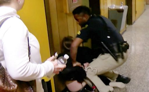 FILE - In this Monday, Jan. 8, 2018, file image made from a video provided by KATC-TV middle-school English teacher Deyshia Hargrave is handcuffed by a city marshal after complying with a marshal's orders to leave a Vermilion Parish School Board meeting in Abbeville, La., west of New Orleans. Louisiana's attorney general sued a local school board Thursday, March 8, 2018, over a meeting disrupted by the video-recorded arrest of Hargrave being roughly handcuffed on a hallway floor after she criticized the district superintendent's pay raise.  Attorney General Jeff Landry's lawsuit accuses the Vermilion Parish School Board and its members of violating the state's Open Meetings Law by stifling public debate at the Jan. 8 meeting. (KATC-TV via AP, File)