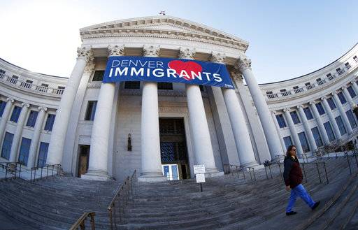 FILE - In this Feb. 26, 2018 file photo, a banner to welcome immigrants is viewed through a fisheye lens over the main entrance to the Denver City and County Building. Four lawmakers from Colorado are meeting with officials at the White House on Thursday, March 8, 2018 to talk about punishing so-called sanctuary cities that limit cooperation with federal immigration officials. Denver has not declared itself to be a sanctuary city but its cooperation with immigration authorities has been criticized by U.S. Attorney Jeff Sessions.