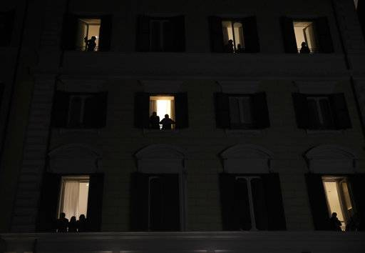 People are silhouetted as they peer out windows to look at a women's demonstration to mark the international Women's Day in Rome, Thursday, March 8, 2018.