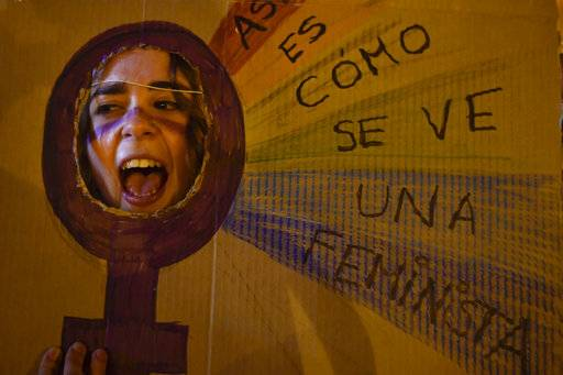 A demonstrator shouts slogans through a piece of cardboard reading on right, ''This is what feminist looks like'' while protesting male violence against women and demanding equality of labour opportunities during the general female strike to commemorate International Women's Day, in Pamplona, northern Spain, Thursday, March 8, 2018. Spanish women are marking International Women's Day with the first-ever full day strike and dozens of protests across the country against wage gap and gender violence.