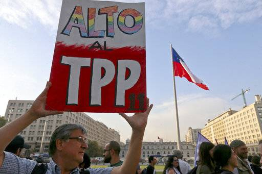 A man holds a sign against the signing of the Trans-Pacific Partnership, TPP, during a demonstration outside La Moneda presidential palace, in Santiago, Chile, Wednesday, March 7, 2018. Protesters voiced their opposition to the signing of the 11-country pact that includes Peru, Mexico, New Zealand, Canada, Australia, Malaysia, Japan, Singapore, Vietnam, Brunei and Chile.