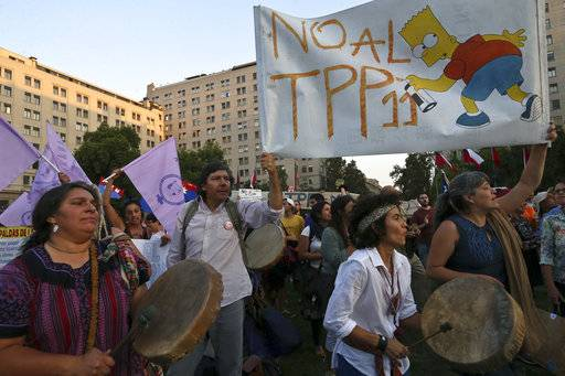 People take part in a demonstration against the Trans-Pacific Partnership, TPP, outside La Moneda presidential palace, in Santiago, Chile, Wednesday, March 7, 2018. Protesters voiced their opposition to the signing of the 11-country pact that includes Peru, Mexico, New Zealand, Canada, Australia, Malaysia, Japan, Singapore, Vietnam, Brunei and Chile.