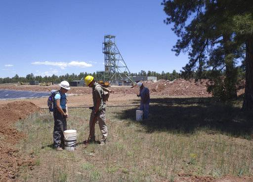 FILE--In this June 7, 2013, fie photo provided by the U.S. Geological Survey, scientists, from left, Christine Dowling, Adam Benthem, and David Naftz collect soil samples on the Canyon Mine property in Arizona. More than a quarter of the way into a 20-year ban on the filing of new mining claims around the Grand Canyon, scientists say they don't have the data they need to show whether uranium negatively is impacting plants, animals and a water source for more than 30 million people. (Katie Walton-Day/U.S. Geological Survey via AP, file)