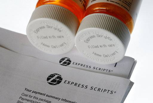 FILE - In this July 25, 2017, file photo, Express Scripts prescription medication bottles are arranged for a photo in Surfside, Fla. Health insurer Cigna will spend about $52 billion to acquire the pharmacy benefits manager Express Scripts, announced Thursday, March 8, 2018, the latest in a string of proposed buyouts and tie-ups in a rapidly shifting landscape for the health services industry.