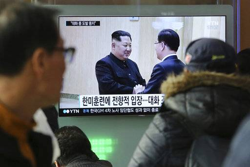 "People watch a TV screen showing North Korean leader Kim Jong Un, left, meeting with South Korean National Security Director Chung Eui-yong in Pyongyang, North Korea, at the Seoul Railway Station in Seoul, South Korea, Wednesday, March 7, 2018. After years of refusal, North Korean leader Kim Jong Un is willing to discuss the fate of his atomic arsenal with the United States and has expressed a readiness to suspend nuclear and missile tests during such talks, a senior South Korean official said Tuesday. Korean characters seen on the screen read: ""South Korea-U.S. joint military drills."""