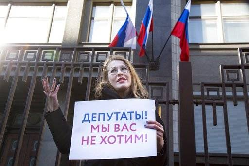 "Russian TV host and presidential candidate Ksenia Sobchak attends an Amnesty International picket against sexual harassment holding a placard reading ""Deputies (lawmakers), we don't want you!"" in front of the Russian State Duma, the Lower House of the Russian Parliament in Moscow, Russia, Thursday, March 8, 2018. Sobchak held her demonstration on Thursday, International Women's Day which is observed as a public holiday in Russia."