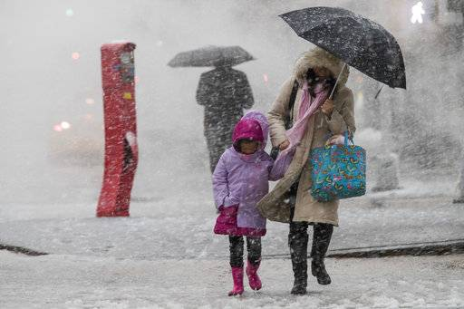 Pedestrians walk along Delancey St. during a snowstorm, Wednesday, March 7, 2018, in New York. The New York metro area was hit with another winter storm Wednesday just days after another nor'easter hammered the region with high winds.