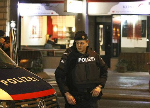 A police officers stands in front of a Japanese restaurant after several people have been injured in a knife attack on the streets of Vienna, Austria, Wednesday, March 7, 2018.