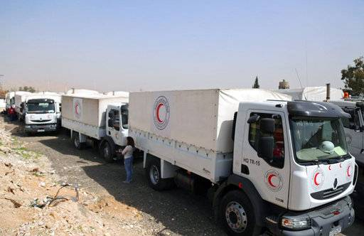 This photo released by the Syrian Red Crescent shows a convoy of vehicles of the Syrian Red Crescent arriving to Douma, eastern Ghouta, a suburb of Damascus, Syria, Monday, March. 5, 2018. Desperate for food and medicine, Syrian civilians in the war-ravaged eastern suburbs of Damascus hoped for relief Monday as a 46-truck aid convoy began entering the rebel stronghold, the first such shipment in months. (Syrian Red Crescent via AP)