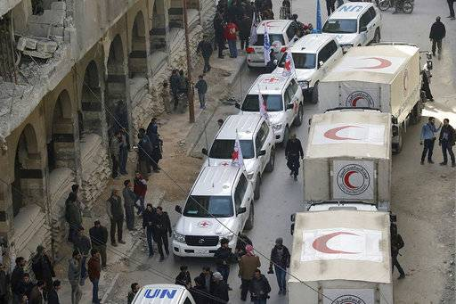 This photo released by the Syrian Red Crescent shows civilians gathering near a convoy of vehicles of the Syrian Red Crescent in Douma, eastern Ghouta, a suburb of Damascus, Syria, Monday, March. 5, 2018. Desperate for food and medicine, Syrian civilians in the war-ravaged eastern suburbs of Damascus hoped for relief Monday as a 46-truck aid convoy began entering the rebel stronghold, the first such shipment in months. (Syrian Red Crescent via AP)