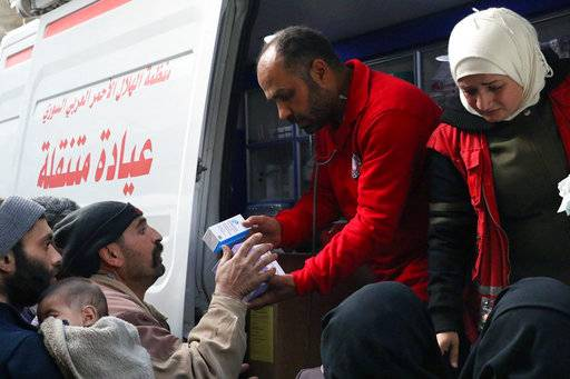 This photo release by the Syrian Red Crescent, shows members of the Syrian Red Crescent distributing medicines for civilians in Douma, eastern Ghouta, a suburb of Damascus, Syria, Monday, March. 5, 2018. Desperate for food and medicine, Syrian civilians in the war-ravaged eastern suburbs of Damascus hoped for relief Monday as a 46-truck aid convoy began entering the rebel stronghold, the first such shipment in months. (Syrian Red Crescent via AP)