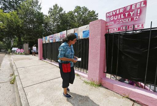 FILE - In this June 30, 2015, file photo, Pam Miller, of Pro Life Mississippi, walks along the fence surrounding as she attempts to counsel a person entering the Jackson Women's Health Organization clinic near downtown Jackson, Miss. The facility is currently Mississippi's only abortion clinic. Abortion law experts say House Bill 1510, which passed the Mississippi Senate Tuesday, March 7, 2018, and is one House vote away from the desk of a governor eager to sign it, is an invitation to the Supreme Court to allow states to begin restricting abortion earlier in pregnancy. The law that passed the Senate would ban most abortions after 15 weeks.