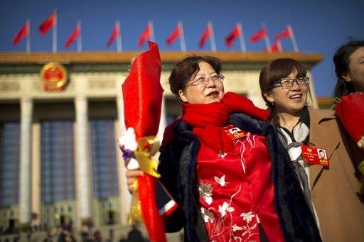 Delegates holding flower bouquets for International Women's Day pose for photos outside of the Great Hall of the People as they arrive for a plenary session of the Chinese People's Political Consultative Conference (CPPCC) in Beijing, Thursday, March 8, 2018. Students at China's prestigious Tsinghua University are celebrating International Women's Day with banners making light of a proposed constitutional amendment to scrap term limits for the country's president.