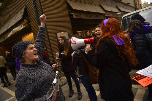 A woman gestures as she protests male violence against women, during a female general strike to commemorate International Women's Day, in Pamplona, northern Spain, Thursday, March 8, 2018.