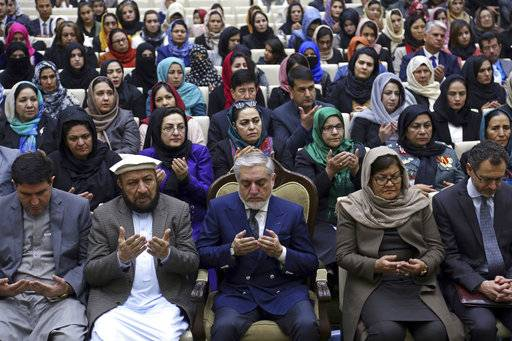 Afghanistan's Chief Executive, Abdullah Abdullah, lower center, prays during an event  marking International Women's Day, in Kabul, Thursday, March 8, 2018.