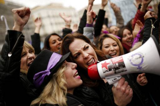 People, mostly women, shout slogans during a protest at the Sol square during the International Women's Day in Madrid, Thursday, March 8, 2018. Spanish women are marking International Women's Day with the first-ever full day strike and dozens of protests across the country against wage gap and gender violence.