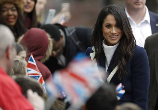 Meghan Markle talks to school children as she arrives with her fiance Britain's Prince Harry to take part in an event for young women as part of International Women's Day in Birmingham, central England Thursday, March 8, 2018.