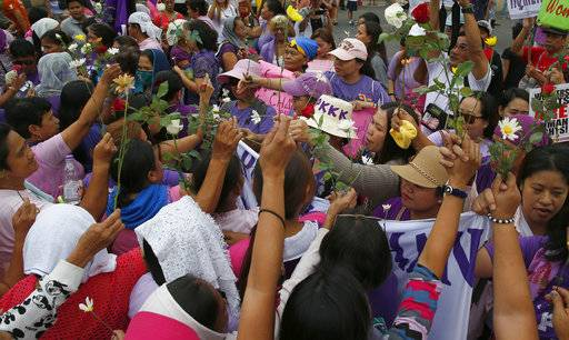 Protesters, right, exchange flowers with families of victims of alleged extra-judicial killings, during a rally to mark International Women's Day Thursday, March 8, 2018 in Manila, Philippines. Hundreds of women activists in pink and purple shirts protested against President Rodrigo Duterte in the Philippines on Thursday, as marches and demonstrations in Asia kicked off International Women's Day.