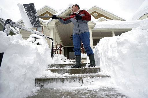 Tom Dubis Shovels off the steps at the Paciorek Funeral Home In Adams, Mass.,Thursday March, 8, 2018.  The Berkshires in Western Massachusetts received 12 to 32 inches of snow overnight. (Ben Garver//The Berkshire Eagle via AP)