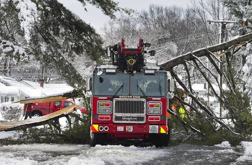 A tree branch fallen from the weight of heavy snow lies on top of a fire truck in East Hartford, Conn., Thursday, March 8, 2018. The branch that fell took down live power lines and landed onto the truck as it was parked responding to a fire. No one was injured. Connecticut's two major utilities were reporting more than 125,000 power outages Thursday morning.   (Jessica Hill/Journal Inquirer via AP)
