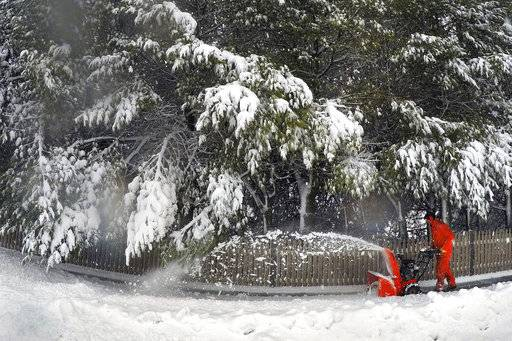 A Portland, Maine resident uses a snowblower to clear snow during a nor'easter, Thursday, March 8, 2018. For the second time in less than a week, a storm rolled into the Northeast with wet, heavy snow Wednesday and Thursday, grounding flights, closing schools and bringing another round of power outages to a corner of the country still recovering from the previous blast of winter.
