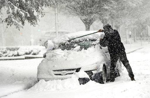 A man clears snow off of his car on State Street in Danbury, Conn., during Wednesday's snowstorm, March 7, 2018. Gov. Dannel P. Malloy has signed an order banning tractor-trailers and tandem trailers on Connecticut highways to help neighboring New York manage its traffic as highway conditions worsen because of the nor'easter. (Carol Kaliff/Hearst Connecticut Media via AP)