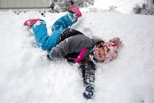 Josslyn Rustay, 6, rolls down the hill above the driveway to her house on West Housatonic Street in Pittsfield on Thursday, March 8, 2018 after the heavy snowfall Wednesday. (Stephanie Zollshan/The Berkshire Eagle via AP)