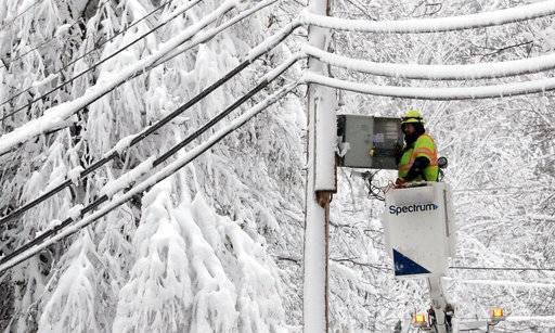 A lineman works to restore power amid limbs sagging with heavy wet snow after a snowstorm, Thursday, March 8, 2018, in Northborough, Mass.  The storm produced heavy, wet snow that brought down tree limbs and power lines.