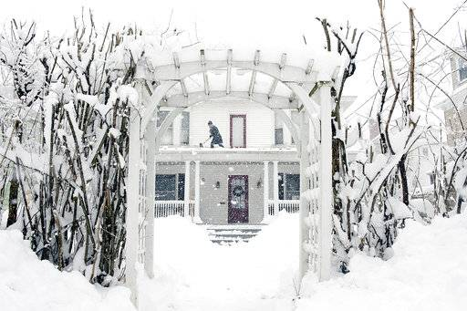 Amber Cox shovels the porch roof at her home in Auburn, Maine, on Thursday, March 8, 2018. The second major storm in less than a week is moving up the East Coast, dumping heavy snow and knocking out power to hundreds of thousands of homes and businesses from Pennsylvania to New England.  (Daryn Slover/Sun Journal via AP)