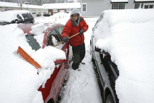Bruno Medina, of Natick, Mass., removes snow from vehicles at a used car lot, Thursday, March 8, 2018, in Natick. For the second time in less than a week, a storm rolled into the Northeast with wet, heavy snow Wednesday and Thursday, grounding flights, closing schools and bringing another round of power outages to a corner of the country still recovering from the previous blast of winter.