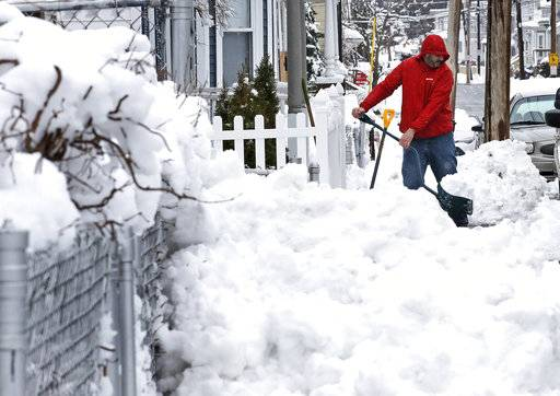Albert Rodriguez shovels a sidewalk in Haverhill, Mass., Thursday, March 8, 2018. An overnight, winter storm blanketed the area with about a foot of snow, causing power outages and the cancellation of school.