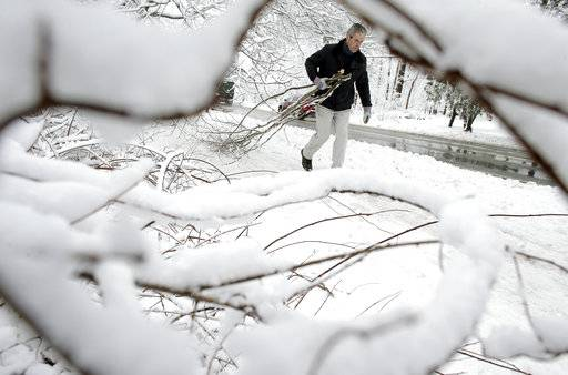 Kevin Crowley, of Weyland, Mass., works to remove damaged tree branches from a driveway, Thursday, March 8, 2018, in Sherborn, Mass. For the second time in less than a week, a storm rolled into the Northeast with wet, heavy snow Wednesday and Thursday, grounding flights, closing schools and bringing another round of power outages to a corner of the country still recovering from the previous blast of winter.