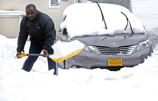 School bus driver Greg Atibu, shovels out his van in Haverhill, Mass., Thursday, March 8, 2018. An overnight, winter storm blanketed the area with about a foot of snow, causing power outages and the cancellation of school.