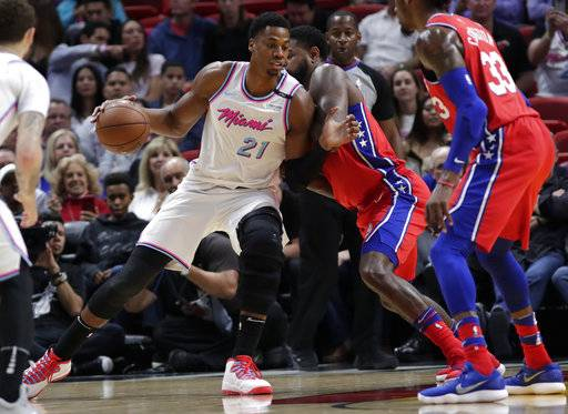 Miami Heat's Hassan Whiteside (21) drives as Philadelphia 76ers' Amir Johnson, center right, defends during the first half of an NBA basketball game Thursday, March 8, 2018, in Miami.