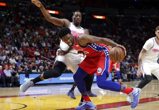 Philadelphia 76ers' Joel Embiid (21) drives as Miami Heat's Bam Adebayo, left, defends during the first half of an NBA basketball game Thursday, March 8, 2018, in Miami.