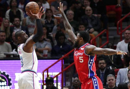 Miami Heat's Dwyane Wade, left, shoots a 3-point basket over Philadelphia 76ers' Amir Johnson (5) during the first half of an NBA basketball game Thursday, March 8, 2018, in Miami.
