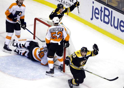 Boston Bruins left wing Brad Marchand, right, celebrates his goal along with Bruins right wing David Pastrnak as Philadelphia Flyers goaltender Alex Lyon (49), center Sean Couturier (14) and defenseman Shayne Gostisbehere (53) react in the final minute of an NHL hockey game Thursday, March 8, 2018, in Boston. The Bruins won 3-2.