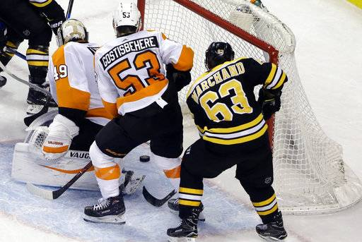 Boston Bruins left wing Brad Marchand (63) scores past Philadelphia Flyers goaltender Alex Lyon (49) as Flyers defenseman Shayne Gostisbehere (53) watches with less than a minute to go in the third period of an NHL hockey game, Thursday, March 8, 2018, in Boston. The Bruins won 3-2.