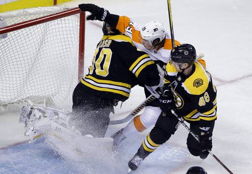 Philadelphia Flyers center Nolan Patrick (19) crashes into Boston Bruins goaltender Tuukka Rask (40) while trying to score as Bruins defenseman Matt Grzelcyk (48) helps to defend during the first period of an NHL hockey game Thursday, March 8, 2018, in Boston.
