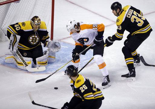 Philadelphia Flyers center Nolan Patrick (19) handles the puck in front of Boston Bruins goaltender Tuukka Rask (40) as Bruins defensemen Zdeno Chara (33) and Brandon Carlo (25) help Rask during the first period of an NHL hockey game Thursday, March 8, 2018, in Boston.