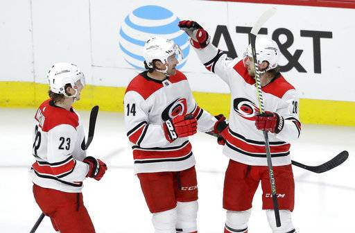 Carolina Hurricanes' Justin Williams (14) celebrates his goal with Brock McGinn, left, and Elias Lindholm during the second period of an NHL hockey game against the Chicago Blackhawks, Thursday, March 8, 2018, in Chicago.