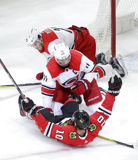 Chicago Blackhawks' Patrick Sharp (10) celebrates his goal as Carolina Hurricanes' Brett Pesce (22) and Jordan Staal react during the first period of an NHL hockey game Thursday, March 8, 2018, in Chicago.