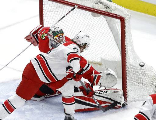 Carolina Hurricanes' Brock McGinn (23) shoots wide of the net as Chicago Blackhawks goaltender J-F Berube defends during the first period of an NHL hockey game Thursday, March 8, 2018, in Chicago.