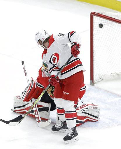 Carolina Hurricanes' Elias Lindholm blocks the view of Chicago Blackhawks goaltender J-F Berube as a shot from Jaccob Slavin scores during the first period of an NHL hockey game Thursday, March 8, 2018, in Chicago.
