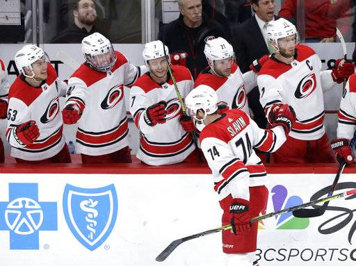 Carolina Hurricanes' Jaccob Slavin (74) celebrates his goal with teammates during the first period of an NHL hockey game against the Chicago Blackhawks, Thursday, March 8, 2018, in Chicago.
